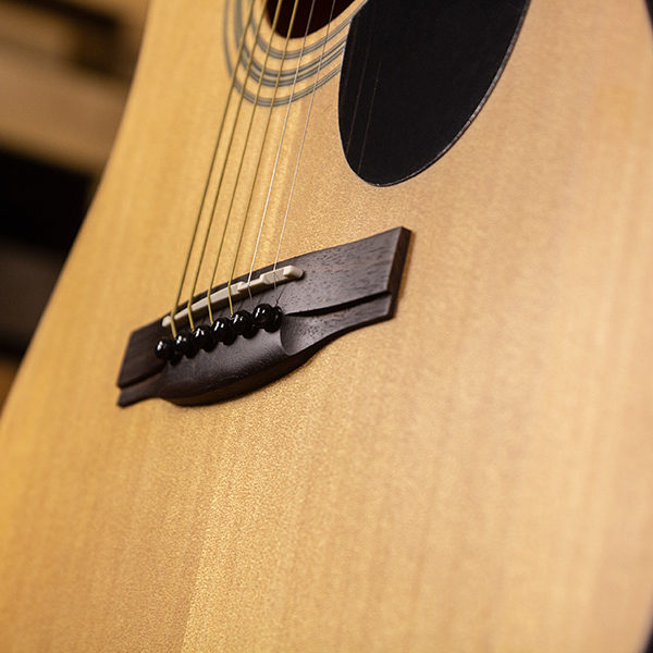 closeup of saddle and bridge on acoustic guitar